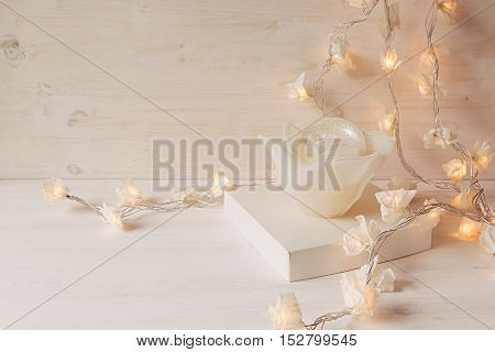 Burning lights and candle rose on white wooden background. Christmas home decor. Interior.