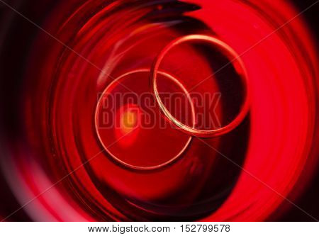 Two gold rings on red background. Close-up.