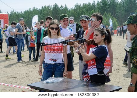 Tyumen, Russia - June 11, 2016: Race of Heroes project on the ground of the highest military and engineering school. Exhibition of weapon. Woman shooting with air rifle gun