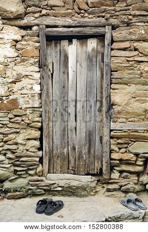 Old Wood Door In Stone Wall with slippers
