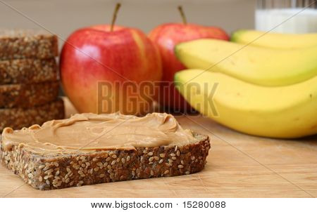 Peanut butter sandwich, apples, bananas and a glass of milk in the background.