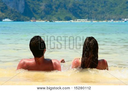 Young couple relaxed side by side in the water on a beach.