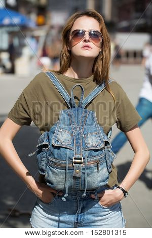 Young woman with pretty cute face in sunglasses in casual green shirt with denim backpack on breast holding her hands in jeans pockets on street background outdoor