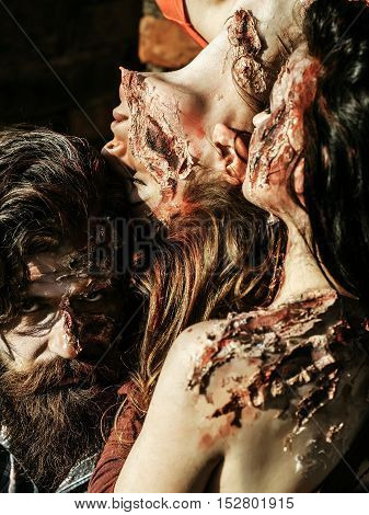 Halloween zombie people of bearded man with beard and young women girls with red blood and wounds outdoors on brick wall