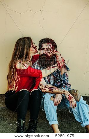 Halloween zombie couple of bearded man hipster or war soldier and bloody young woman with wounds and red blood sit on beige wall