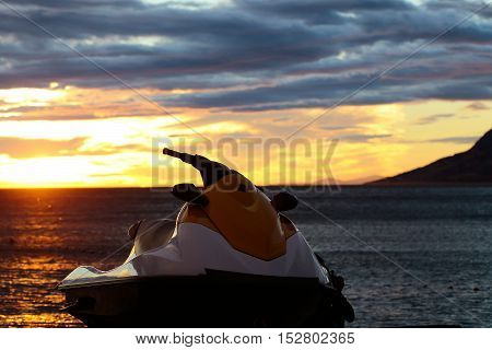 red scooter over dark twilight sky on beach with sea or ocean water on evening sunset natural background