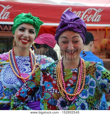 Grodno, Belarus - June 4, 2016: 11 Festival of National Cultures in Grodno, Belarus. Two young smiling women in Venezuelan multicolored traditional costumes with hairstyles and makeup.
