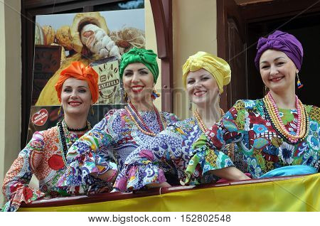 Grodno, Belarus - June 4, 2016: 11 Festival of National Cultures in Grodno, Belarus. Four young smiling woman in the Venezuelan multicolored traditional costumes with hairstyles and makeup.