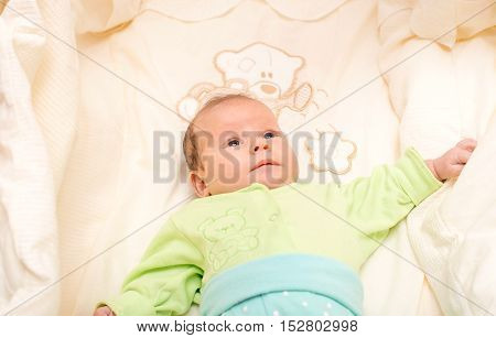 baby girl lying and playing in her crib