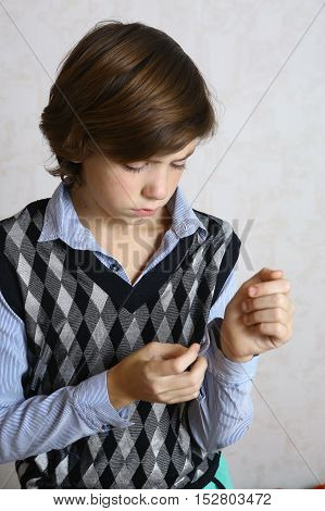 preteen handsome boy getting dressed close up photo boy put on shirt