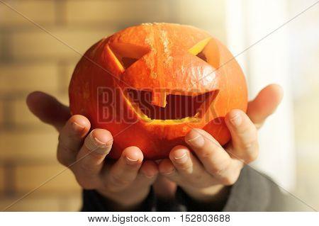 cheerful orange pumpkin in the hands / Halloween holiday spirit