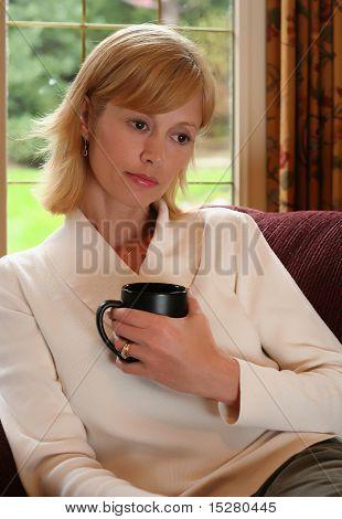 Frau in tief dachte entspannen auf dem Sofa.