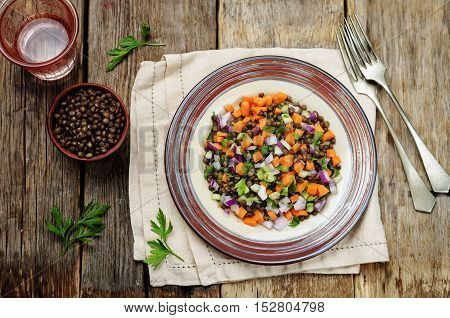green lentils carrots celery salad on wood background