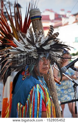 Grodno, Belarus - June 25, 2016: The city festival of street art in Grodno in June 2016. Redskin man in the national Indian suit and headdress with feathers plays in instrument on the street.