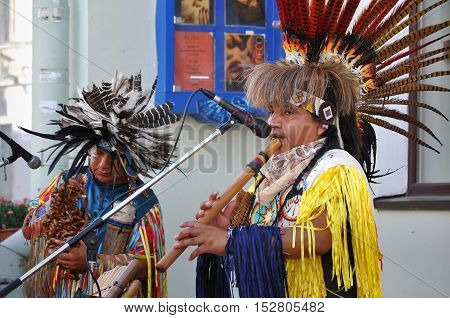 Grodno, Belarus - June 25, 2016: The city festival of street art in Grodno in June 2016. Two redskin people in the national Indian suit and headdress with feathers play an instrument on the street.