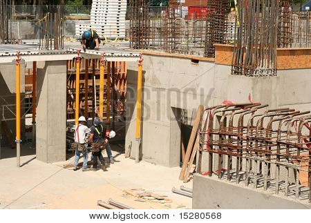Four men at work at a highrise construction site.
