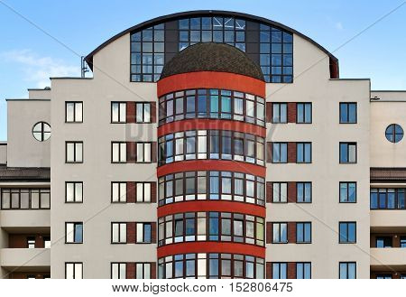 Grodno, Belarus - August 11, 2016: Front view of multistory modern residential building. White facade with circular roof rounded balconies and glazing. Grodno, Belarus.