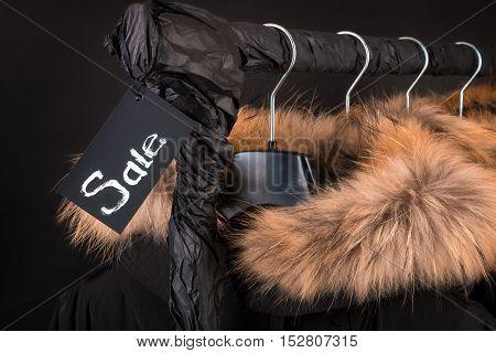 Lot Of Black Coats, Jacket With Fur On Hood Hanging  Clothes Rack.  Background. Sale Inscription.  F