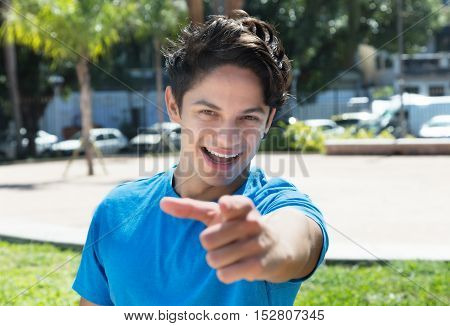 Caucasian guy in a blue shirt pointing at camera outdoor in the city in the summer