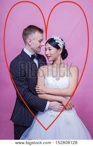 Loving bridegroom holding flower while looking at bride against pink background with red heart drawn around them