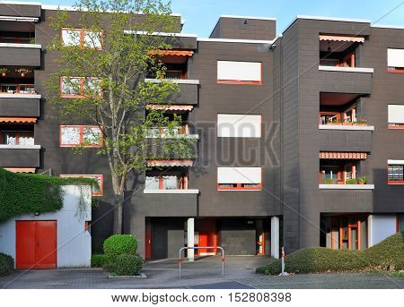 Stuttgart, Germany - April 21, 2016: A modern high-rise apartment building in black with red windows balconies and green plants. Front view.