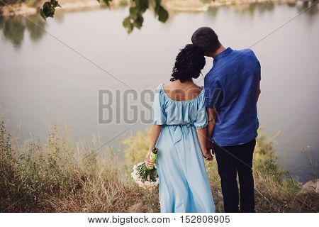 A Wedding By The Sea. Honeymoon. The Bride And Groom Hugging On The Shore Of Lake. Groom And Bride H