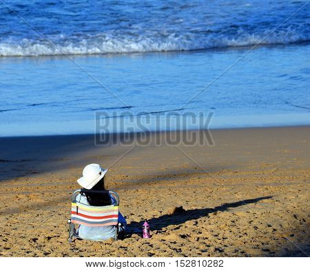 Girl sitting alone on the beach and watching the sea.