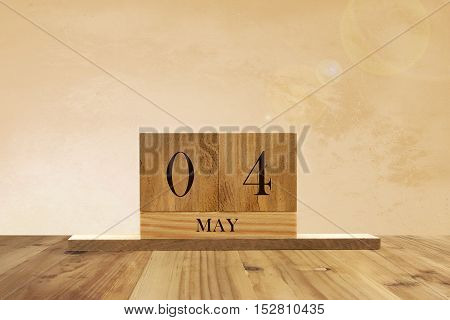 Cube shape calendar for May 04 on wooden surface with empty space for text.