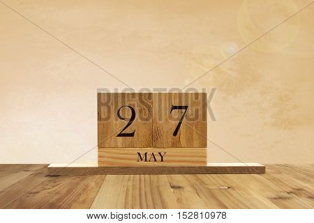 Cube shape calendar for May 27 on wooden surface with empty space for text.