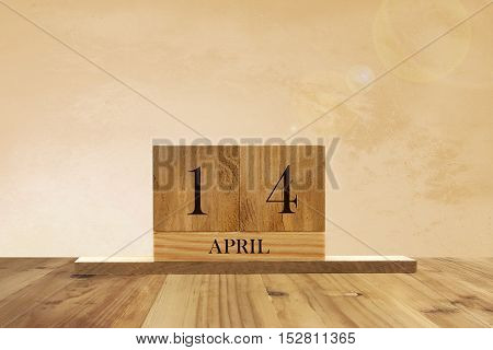 Cube shape calendar for April 14 on wooden surface with empty space for text.
