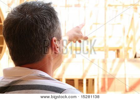 Man pointing at a house under construction.