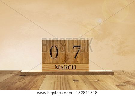 Cube shape calendar for March 07 on wooden surface with empty space for text.