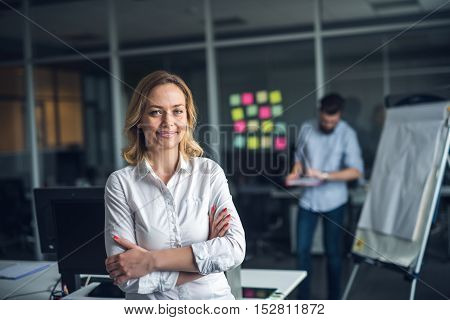 Young and confident businesswoman standing with crossed arms.