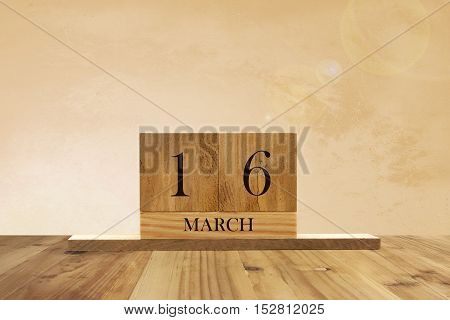Cube shape calendar for March 16 on wooden surface with empty space for text.