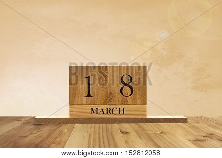 Cube shape calendar for March 18 on wooden surface with empty space for text.