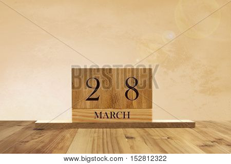 Cube shape calendar for March 28 on wooden surface with empty space for text.