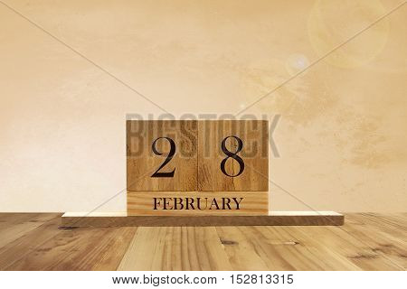 Cube shape calendar for February 28 on wooden surface with empty space for text.