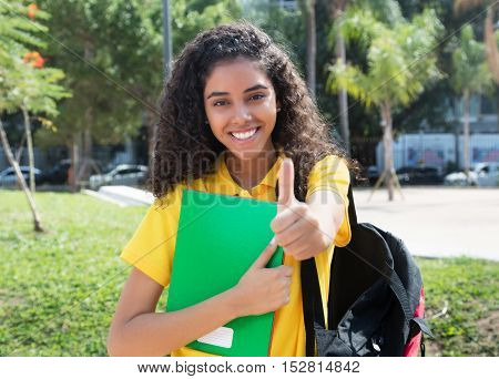 Latin american female student with long dark hair showing thumb outdoor in the summer in the city