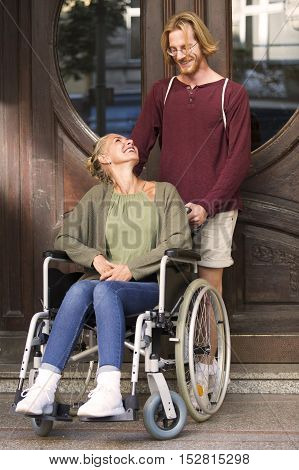 woman in wheelchair at an entrance with a young man helping her