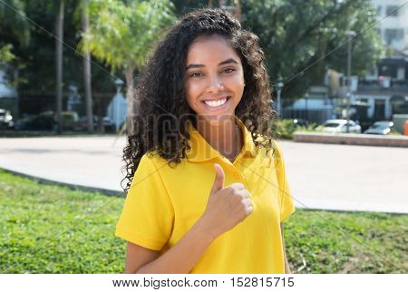 Laughing latin american girl with long dark hair showing thumb outdoors in the summer in the city