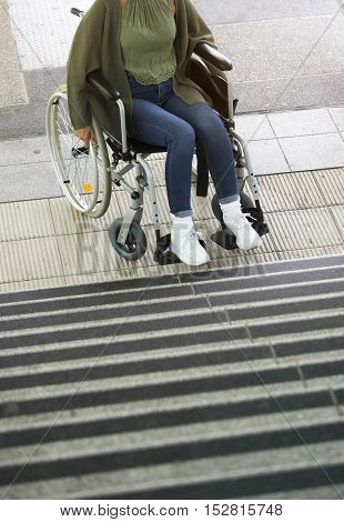 woman in a wheelstair in front of stairs outdoors