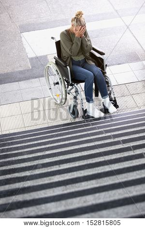 woman in wheelchair in front of stairs outdoors looking desperate