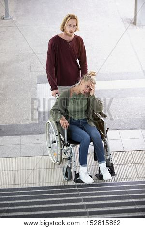 woman in wheelchair in front of stairs outside