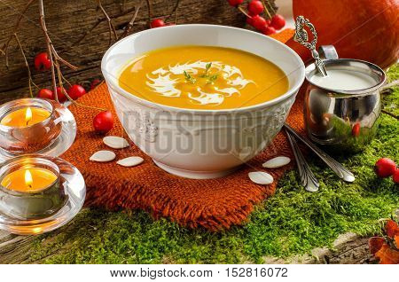 Pumpkin soup in white bowl. Background - rustic style - the old Board and moss. Cream in a small pitcher. Silverware. Candles. Autumn yellow leaves. Selective focus.
