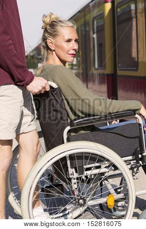 woman in wheelchair at train station with someone helping her