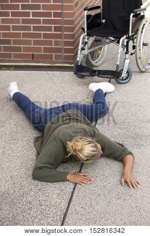 blond woman lying on the pavement next to a wheelchair