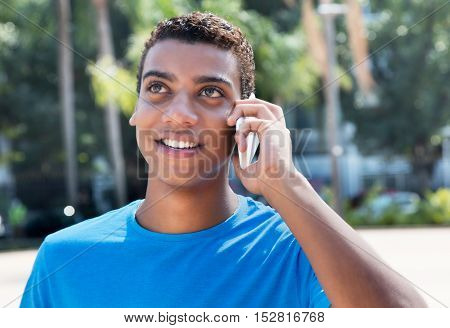 Young latin american hipster using phone outdoor in the city in the summer