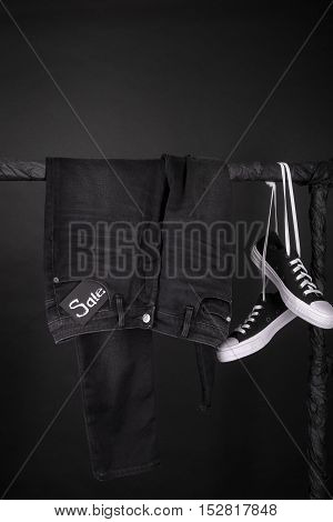 Sale sign. Black friday. Black and white sneakers and pant jeans hanging on clothes rack on black background. Close up.