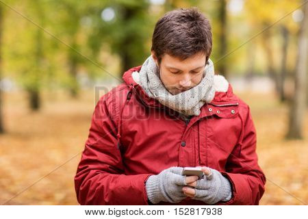 technology, communication and people concept - young man with smartphone walking at autumn park