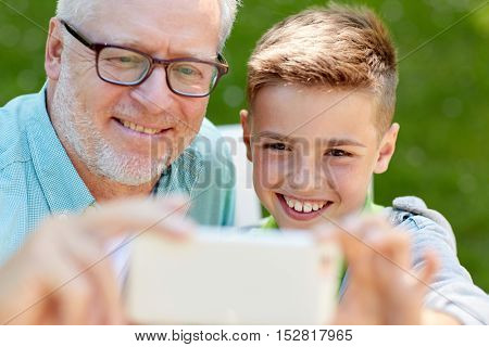family, generation, technology and people concept - happy grandfather and grandson with smartphone taking selfie at summer park